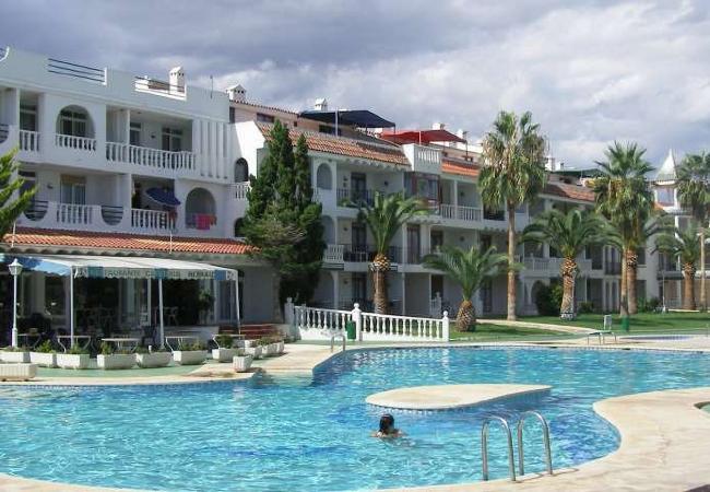 Frente a la playa de la Romana y con una amplia zona ajardinada con piscinas